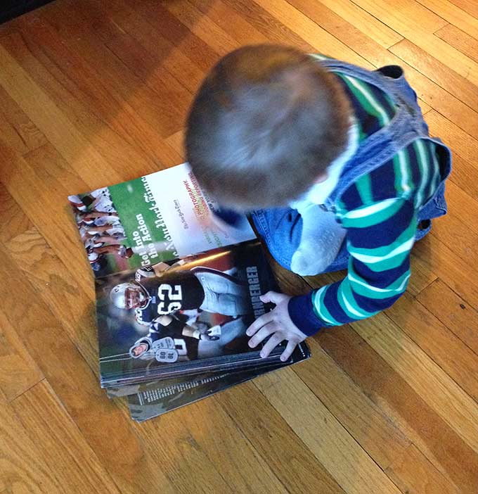 Biggest Little Fan. Hudson loves a good football game, the Pats in particular. Then we noticed him with the old 2010 New England Patriots yearbook.