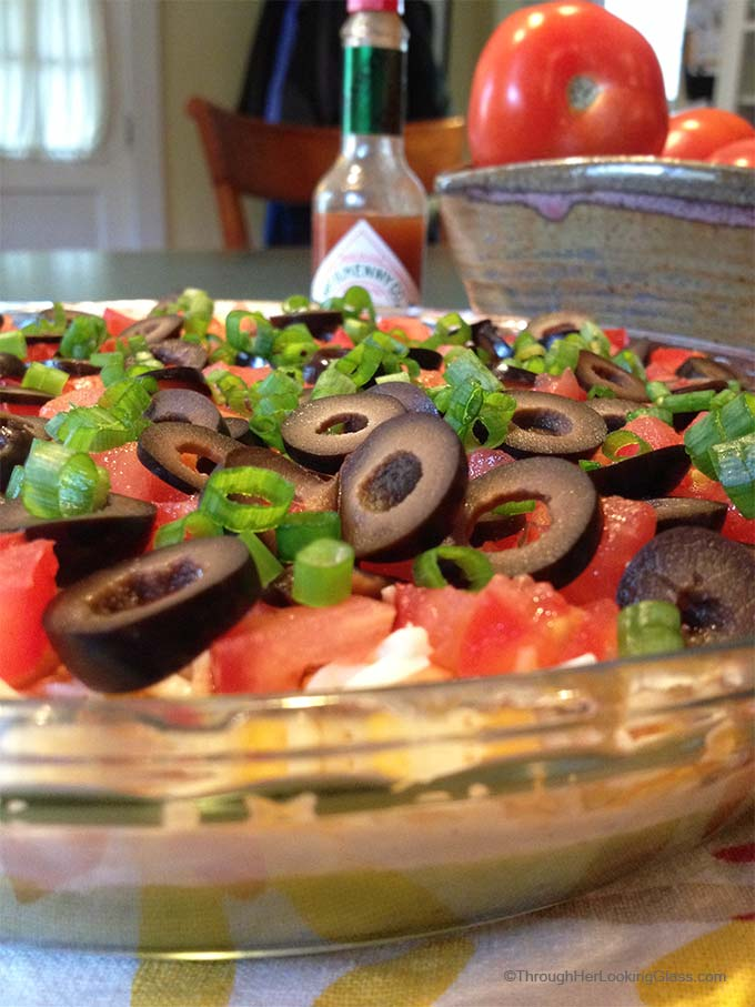 San Francisco Layer Dip: zippy guacamole dip with greek yogurt, taco seasoning, cheese, tomatoes, olives, green onions and hot pepper sauce.