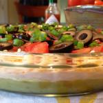 San Francisco Avocado Dip: zippy guacamole dip with greek yogurt, taco seasoning, cheese, tomatoes, olives, green onions and hot pepper sauce.