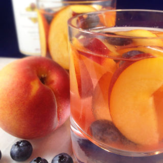 Easy and fruity: Make White Wine Peach Sangria by the pitcherful! Sweet peaches macerate in a delicious cocktail for all the pool & patio summer parties!