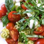 This Caprese Pasta Salad Recipe: perfect side incorporating your garden basil! Fresh basil pesto, pasta, sun-ripened tomatoes and fresh mozzarella. Delish!