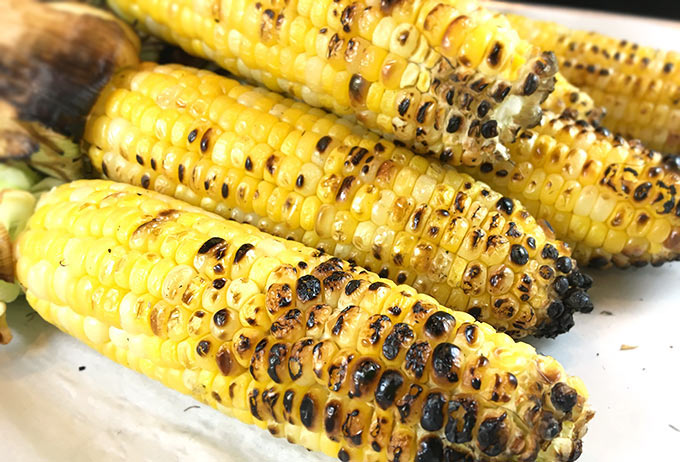 This Charred Mexican Street Corn Recipe is so easy! Grilled corn on the cob w/crumbled cotija, sprinkled w/chili powder, spritzed with lime. Heavenly!
