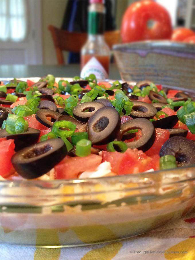 San Francisco Layer Dip: zippy guacamole dip with greek yogurt, taco seasoning, cheese, tomatoes, olives, green onions and hot pepper sauce.