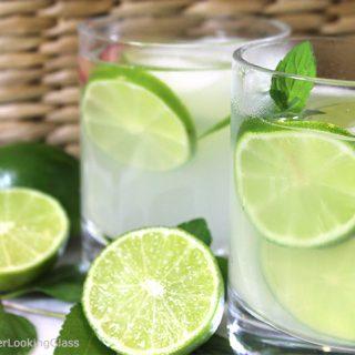 limeade in white glasses with slices of lemon inside