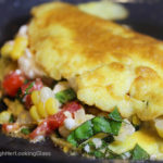 This Summer Corn Basil Tomato & Feta Easy Omelette Recipe is sure to please your friends and family for breakfast, lunch or dinner. Summer corn and juicy, ripe tomatoes combine with fresh garden basil and salty feta for a flavor-full omelette.
